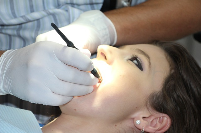 Image of an adult getting their teeth cleaned.