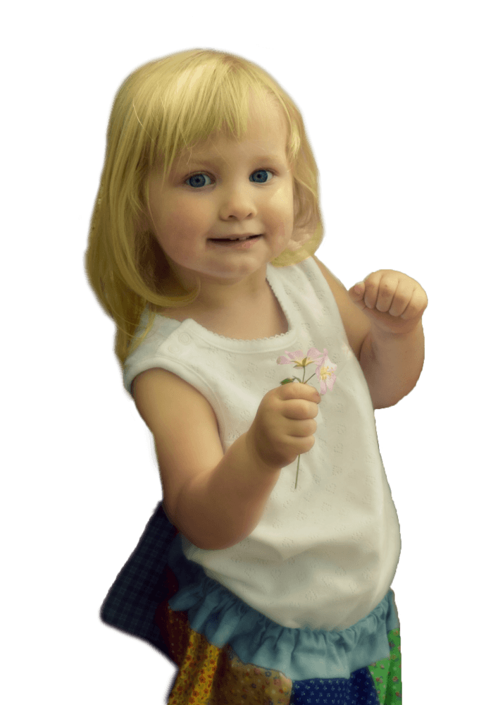 This is an image of a toddler smiling holding a flower.